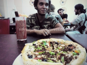 Abdelmalek Boutalliss with milkshake and pizza in ar-Raqqah
